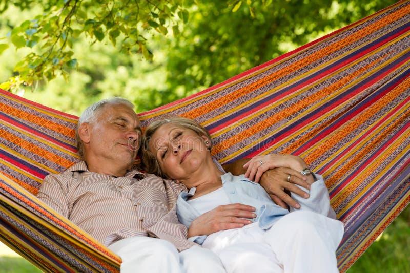 Couples supérieurs détendant dans l'hamac photographie stock