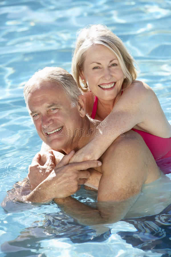 Couples supérieurs détendant dans la piscine ensemble photo stock