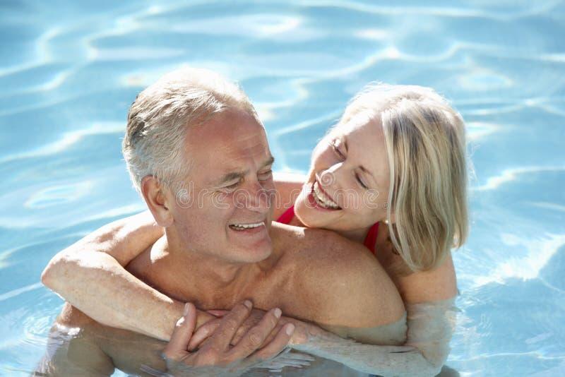 Couples supérieurs détendant dans la piscine ensemble photos stock