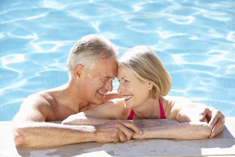 Couples supérieurs détendant dans la piscine ensemble images libres de droits