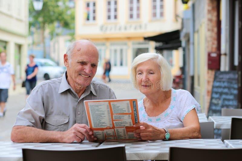 Couples supérieurs détendant en café d'extérieur photographie stock libre de droits