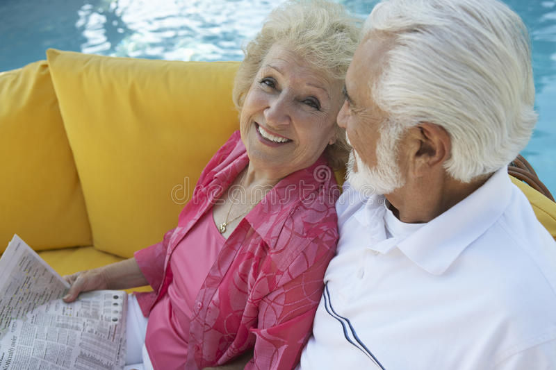 Couples supérieurs détendant par la piscine photo stock