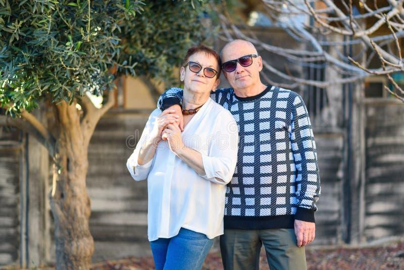 Couples supérieurs détendant par le parc le jour ensoleillé photographie stock libre de droits