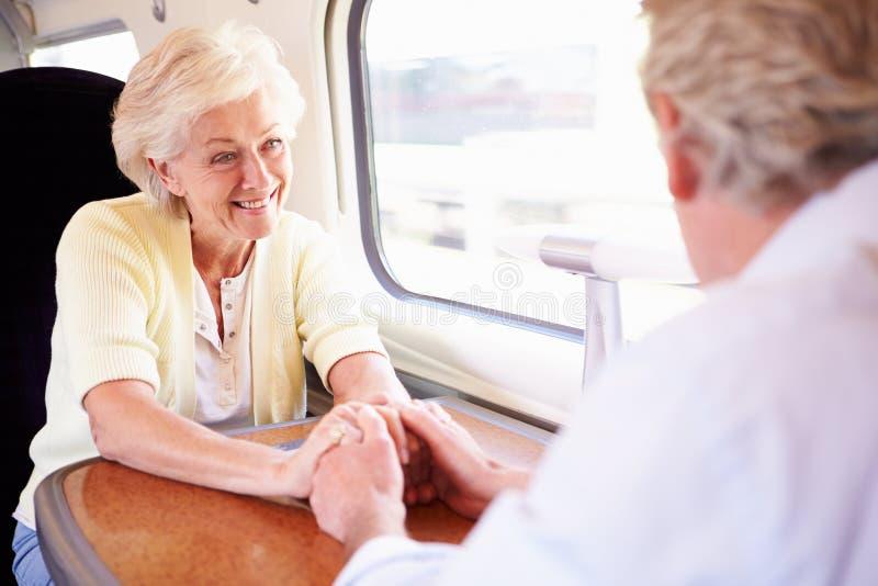 Couples supérieurs détendant sur le voyage en train photos stock