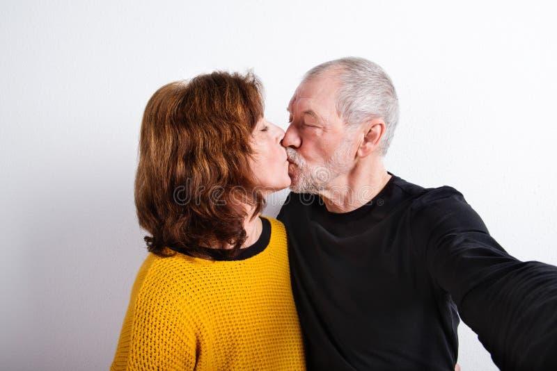 Couples supérieurs dans des baisers d'amour, prenant le selfie Projectile de studio images stock