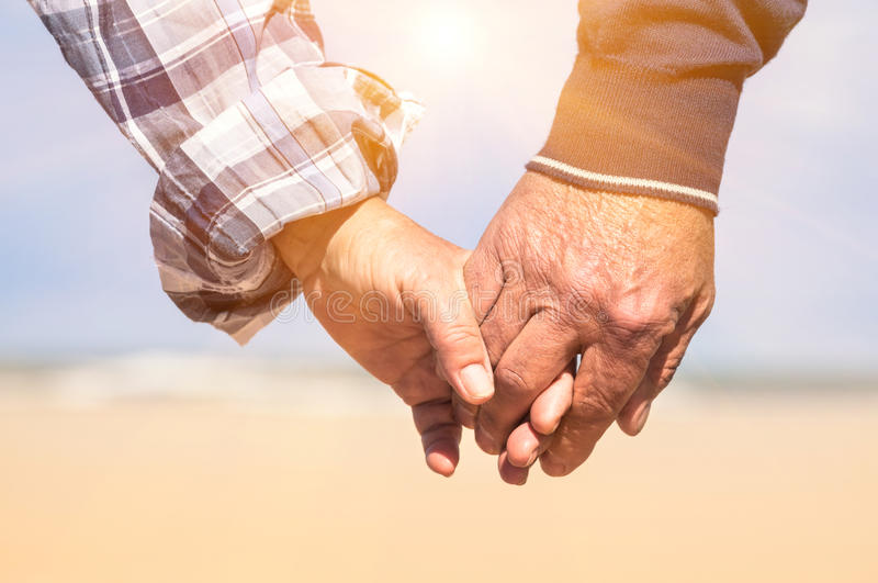 Couples supérieurs dans l'amour marchant à la plage tenant des mains images stock