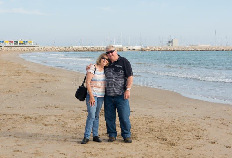 Couples supérieurs dans l'amour marchant sur la plage ayant l'amusement dans un jour ensoleillé photos libres de droits