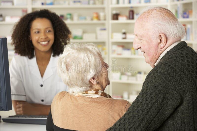 Couples supérieurs dans la pharmacie avec le pharmacien image libre de droits