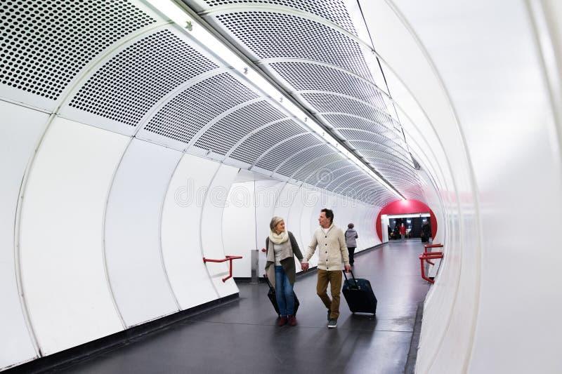 Couples supérieurs dans le couloir du souterrain tirant le bagage de chariot photo stock
