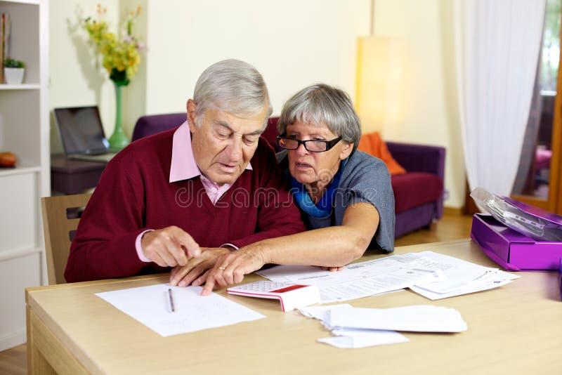 Couples supérieurs dans les factures et les impôts calculateurs de problème photographie stock libre de droits