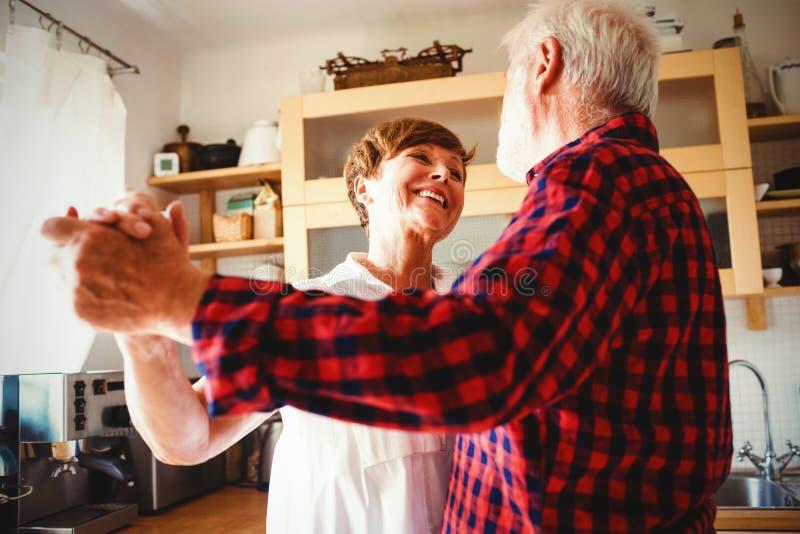 Couples supérieurs dansant ensemble dans la cuisine photos libres de droits