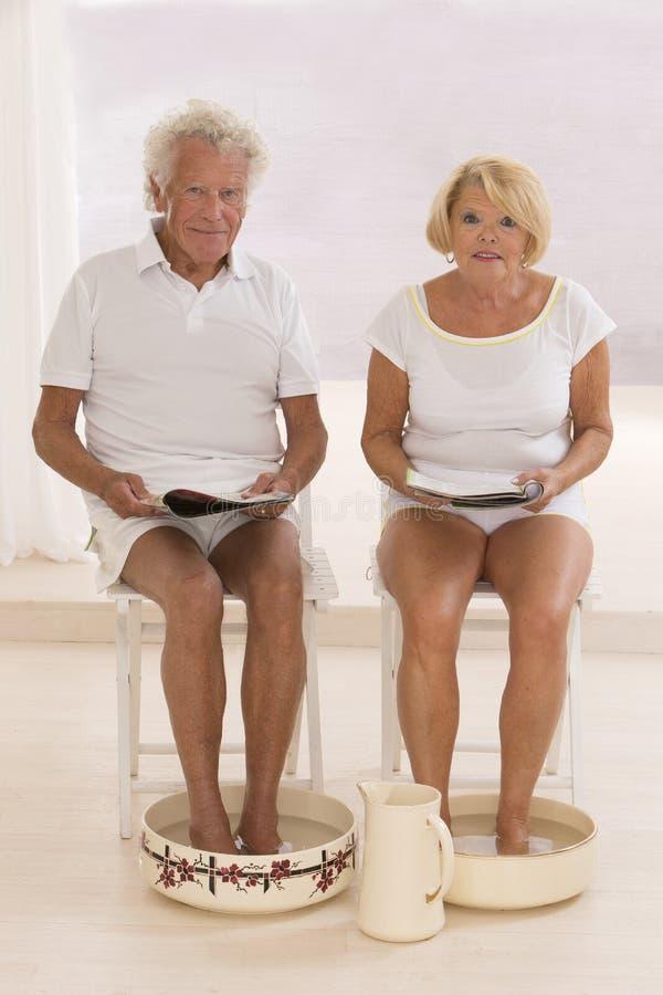 Couples supérieurs de Bath de pied prenant soin de leurs pieds images stock