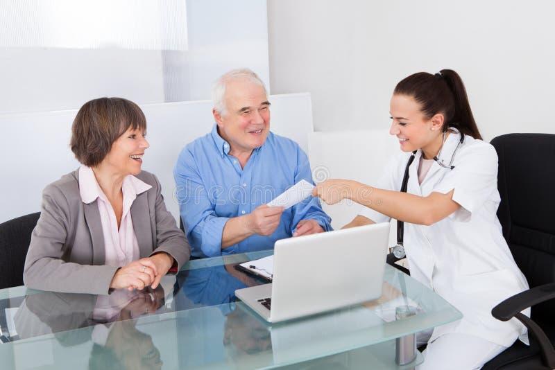 Couples supérieurs de docteur Giving Prescription To dans la clinique photographie stock libre de droits