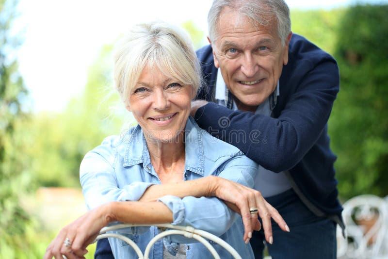Couples supérieurs de sourire dans le jardin photographie stock libre de droits