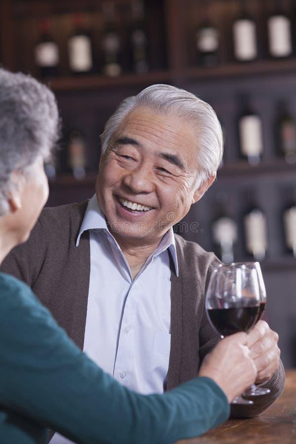 Couples supérieurs de sourire grillant et s'amusant vin potable, foyer sur le mâle photos libres de droits