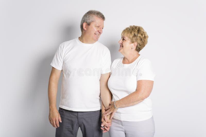 Couples supérieurs de sourire heureux se tenant ensemble sur le fond blanc photo libre de droits