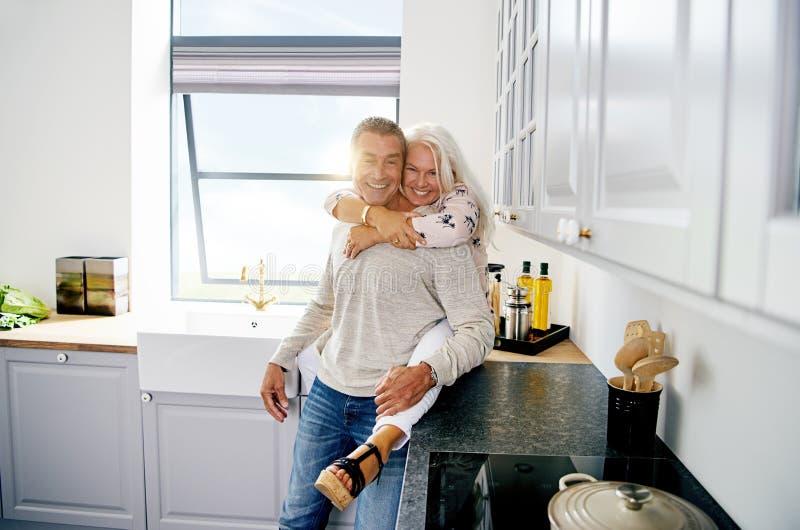 Couples supérieurs de sourire partageant un moment dans leur cuisine photo libre de droits