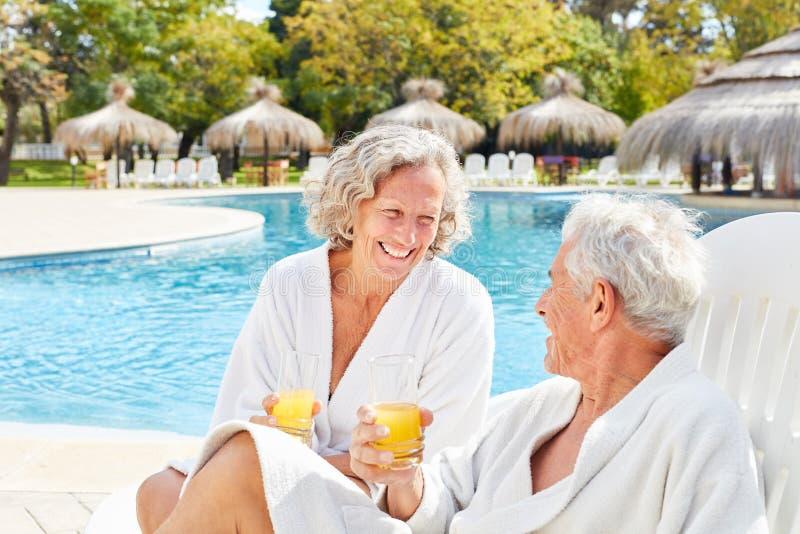 Couples supérieurs des vacances de station thermale détendant par la piscine photos libres de droits