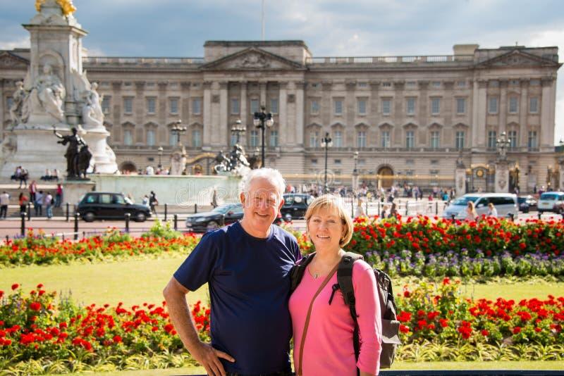Couples supérieurs devant le Buckingham Palace image libre de droits