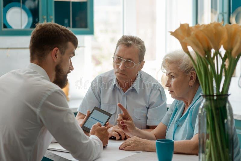 Couples supérieurs discutant avec le conseiller images stock