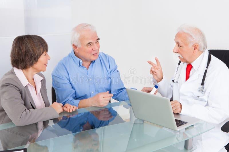 Couples supérieurs discutant avec le docteur images libres de droits