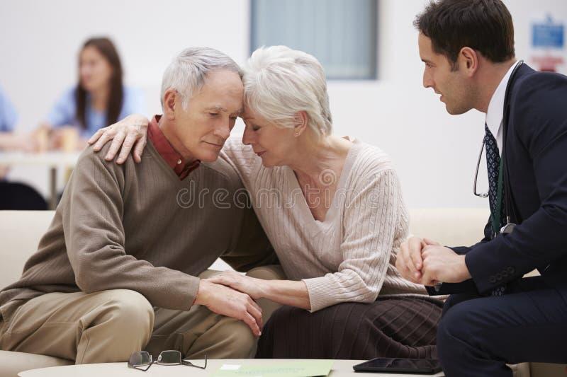Couples supérieurs discutant des résultats d'essai avec le docteur photos stock