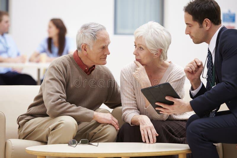 Couples supérieurs discutant des résultats d'essai avec le docteur images stock