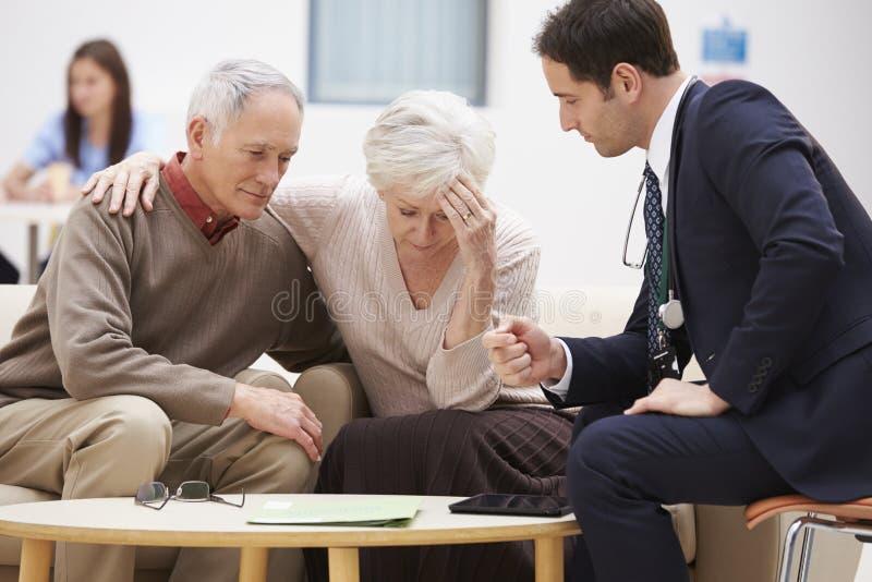 Couples supérieurs discutant des résultats d'essai avec le docteur photographie stock