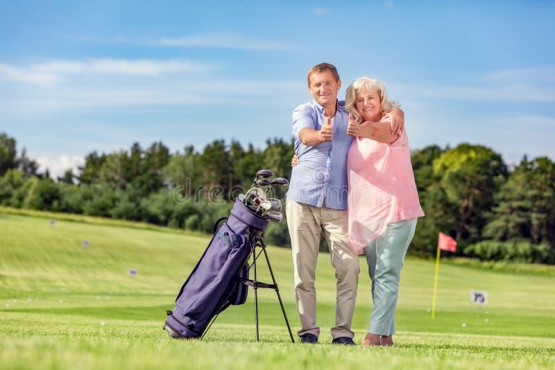 Couples supérieurs donnant des pouces sur un terrain de golf photographie stock
