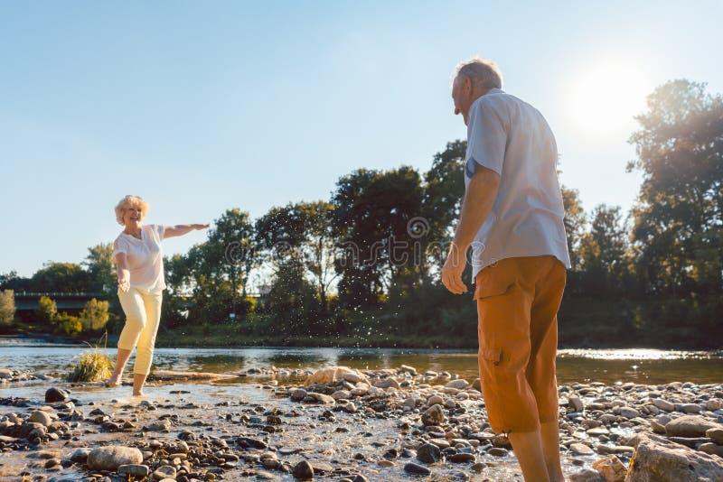 Couples supérieurs drôles jouant avec de l'eau à la rivière dans un jour ensoleillé photo stock