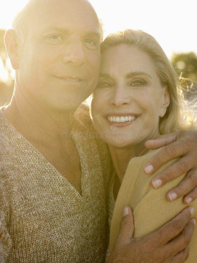 Couples supérieurs embrassant au coucher du soleil sur la plage photographie stock