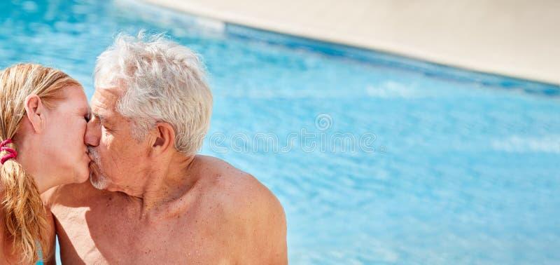 Couples supérieurs embrassant dans la piscine d'hôtel images stock