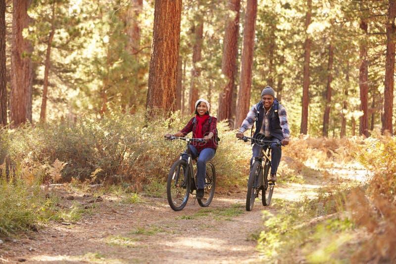 Couples supérieurs faisant un cycle par la région boisée d'automne photo libre de droits