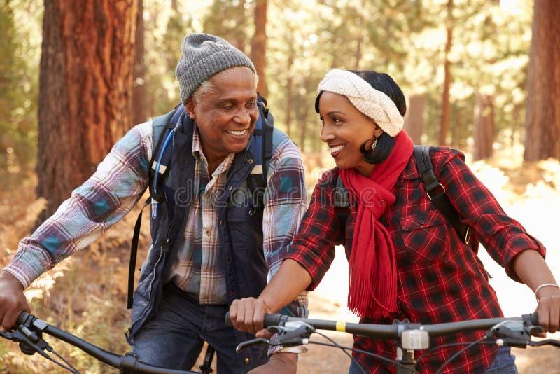 Couples supérieurs faisant un cycle par la région boisée d'automne images stock