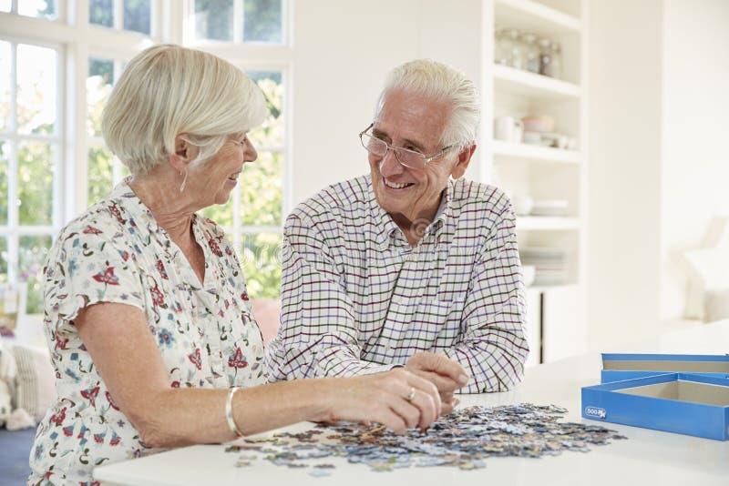 Couples supérieurs faisant un puzzle denteux à la maison image libre de droits
