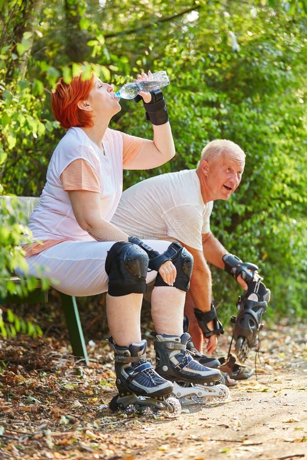 Couples supérieurs faisant une pause du patinage images stock