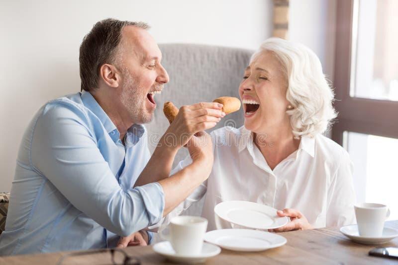 Couples supérieurs gais mangeant le croissant image stock