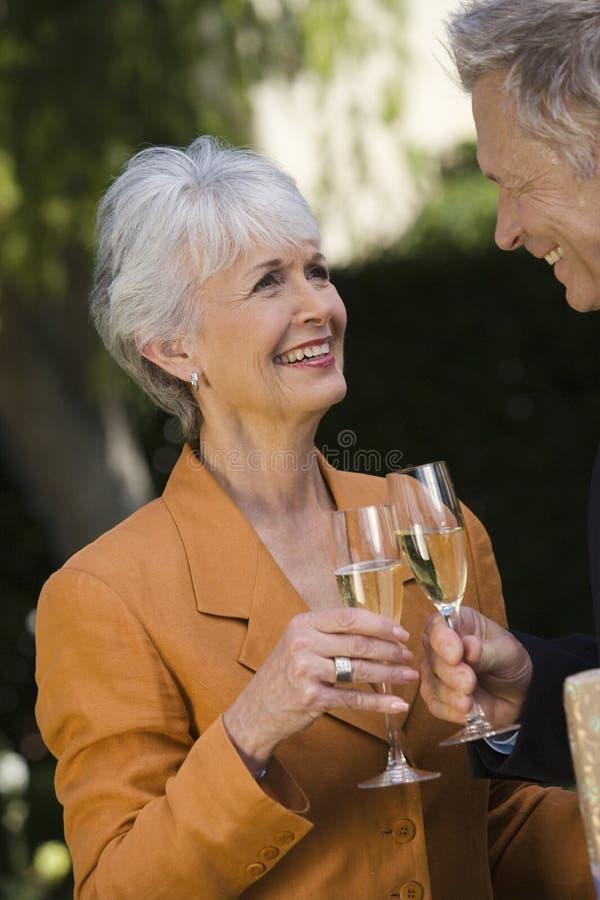 Couples supérieurs grillant Champagne images libres de droits
