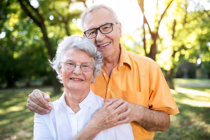 Couples supérieurs heureux étreignant en parc photos stock