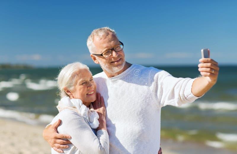 Couples supérieurs heureux étreignant sur la plage d'été photos libres de droits