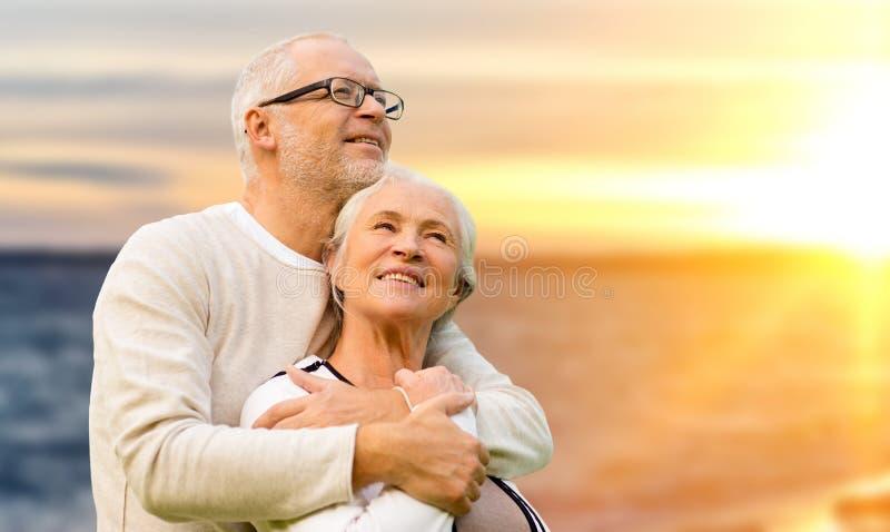 Couples supérieurs heureux au-dessus de fond de coucher du soleil images libres de droits