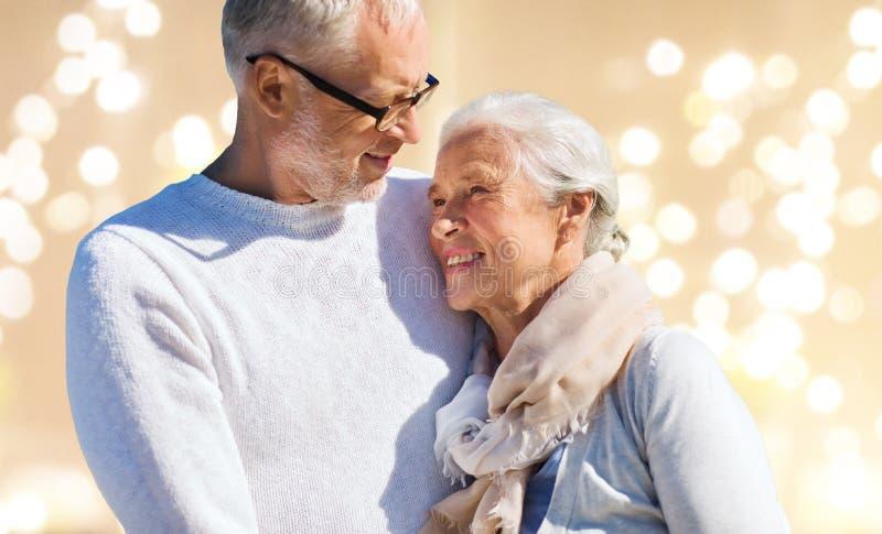 Couples supérieurs heureux au-dessus de fond de fête de lumières photos stock
