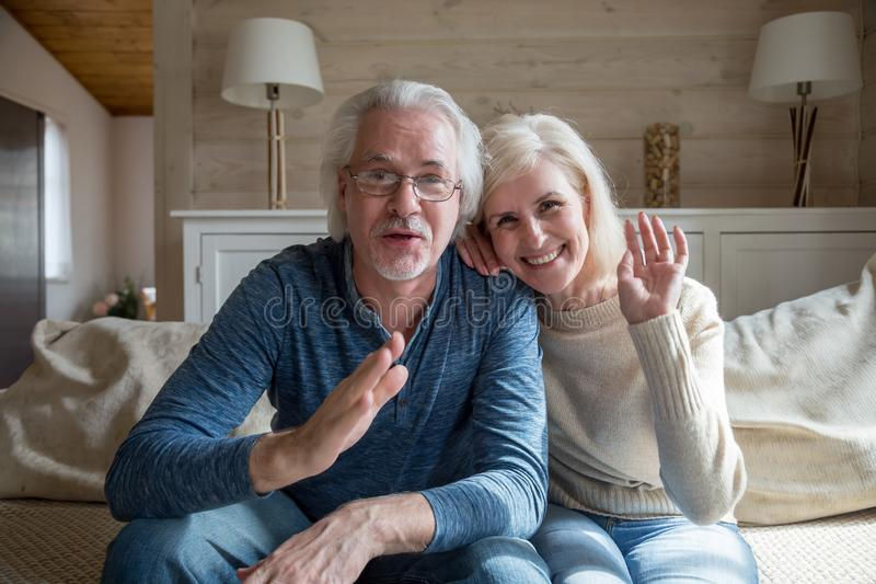 Couples supérieurs heureux ayant l'appel visuel parlant de la maison images libres de droits