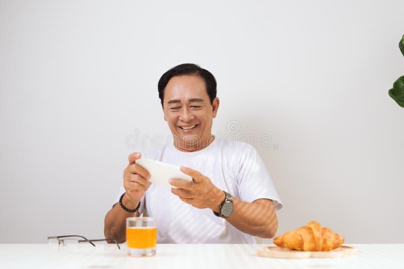 Couples supérieurs heureux ayant le petit déjeuner de croissant à la maison et la boisson photos stock