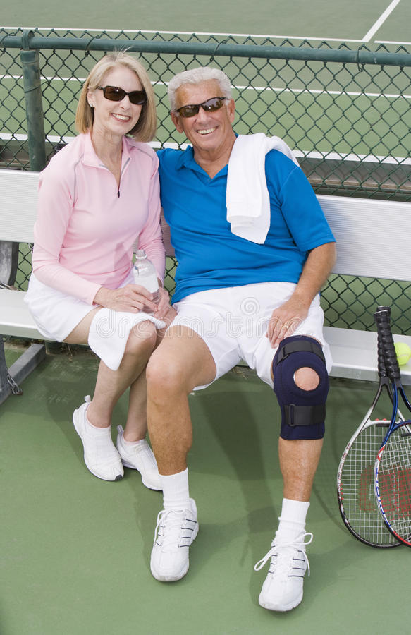 Couples supérieurs heureux détendant après avoir joué le tennis photographie stock