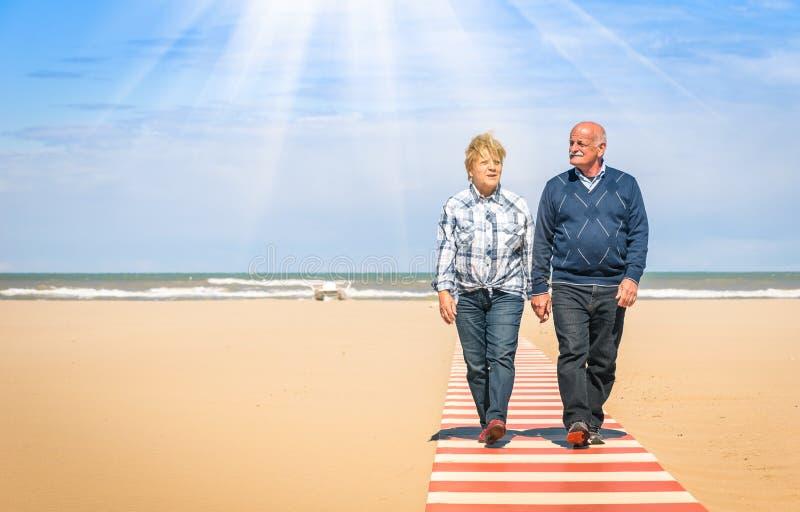 Couples supérieurs heureux dans l'amour marchant de pair à la plage photographie stock