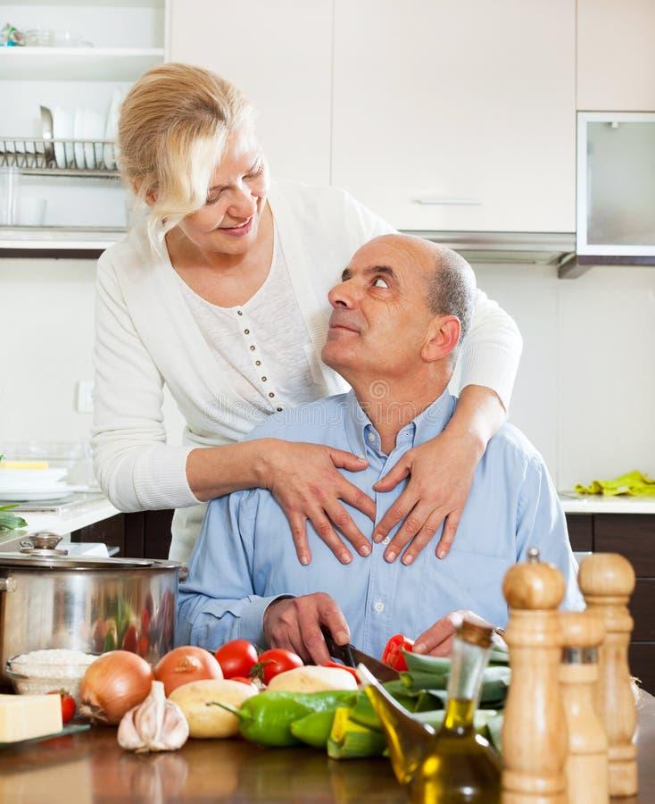Couples supérieurs heureux dans la cuisine préparant le déjeuner images stock