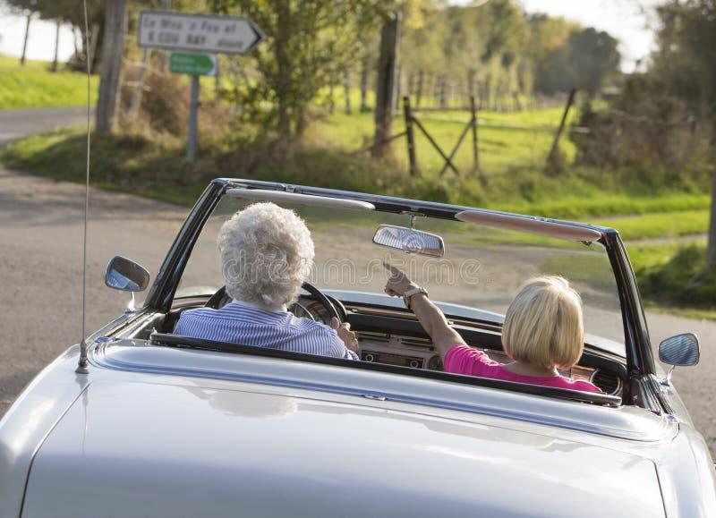 Couples supérieurs heureux dans la voiture de sport de vintage images stock