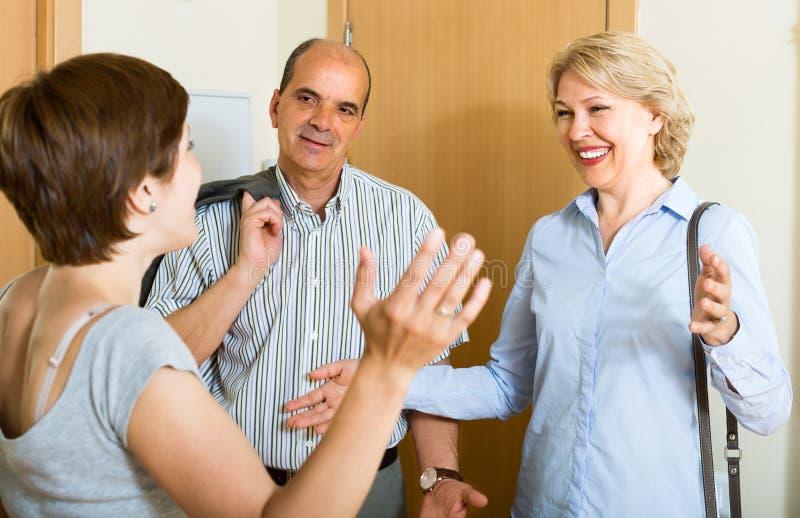 Couples supérieurs heureux de famille rendant visite à la fille adulte image libre de droits