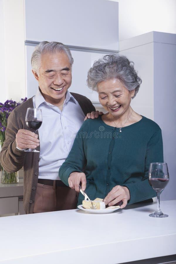 Couples supérieurs heureux de sourire dans le vin et couper en tranches potables de cuisine le fromage photos stock
